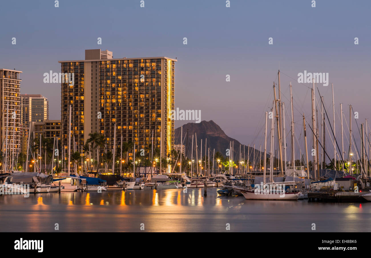 Skyline of Waikiki, Honolulu at night with Ala Moana harbor and Hilton Hawaiian Village resort hotels Stock Photo