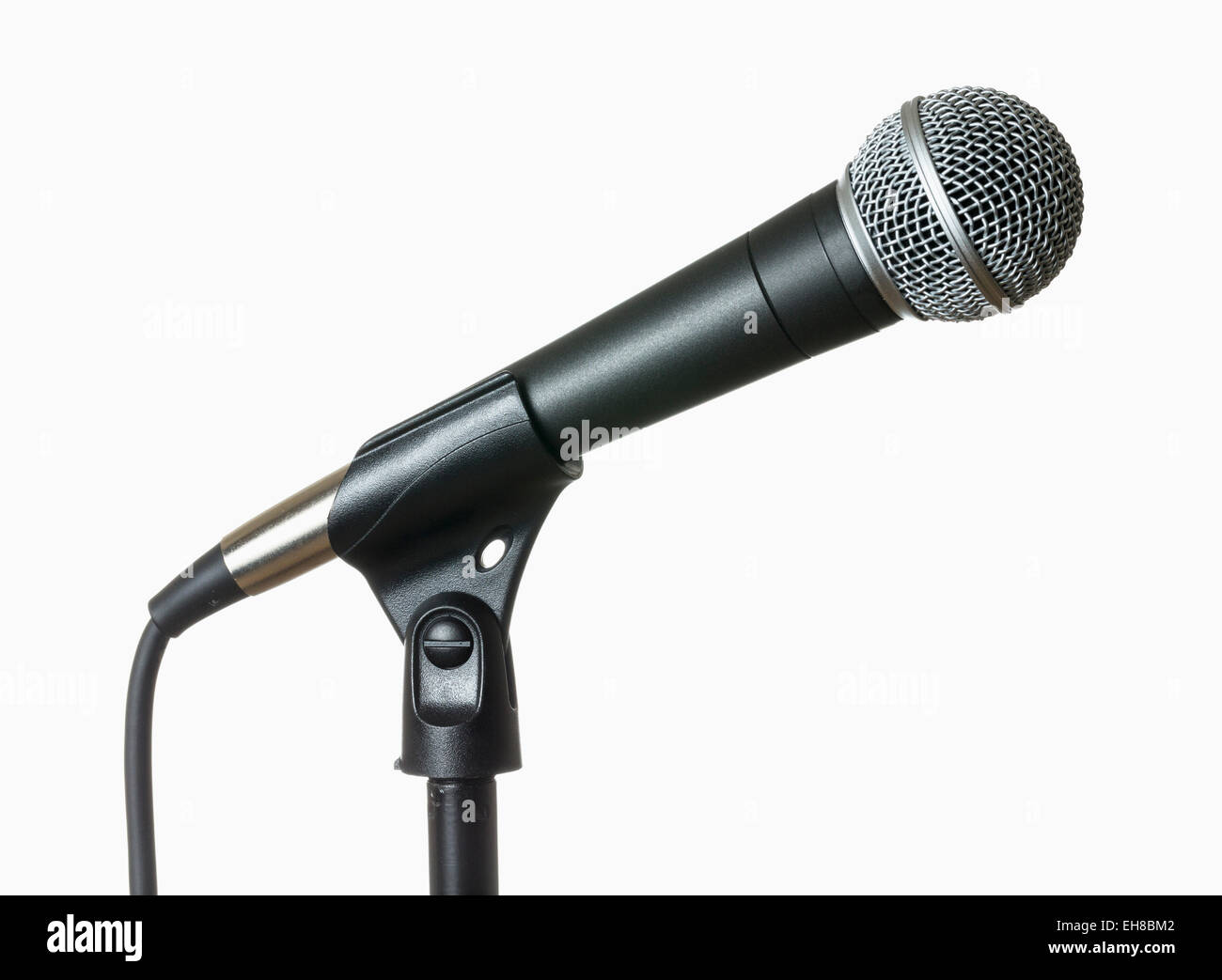 Classic stage microphone in a stand with cable isolated against white - Stock Image