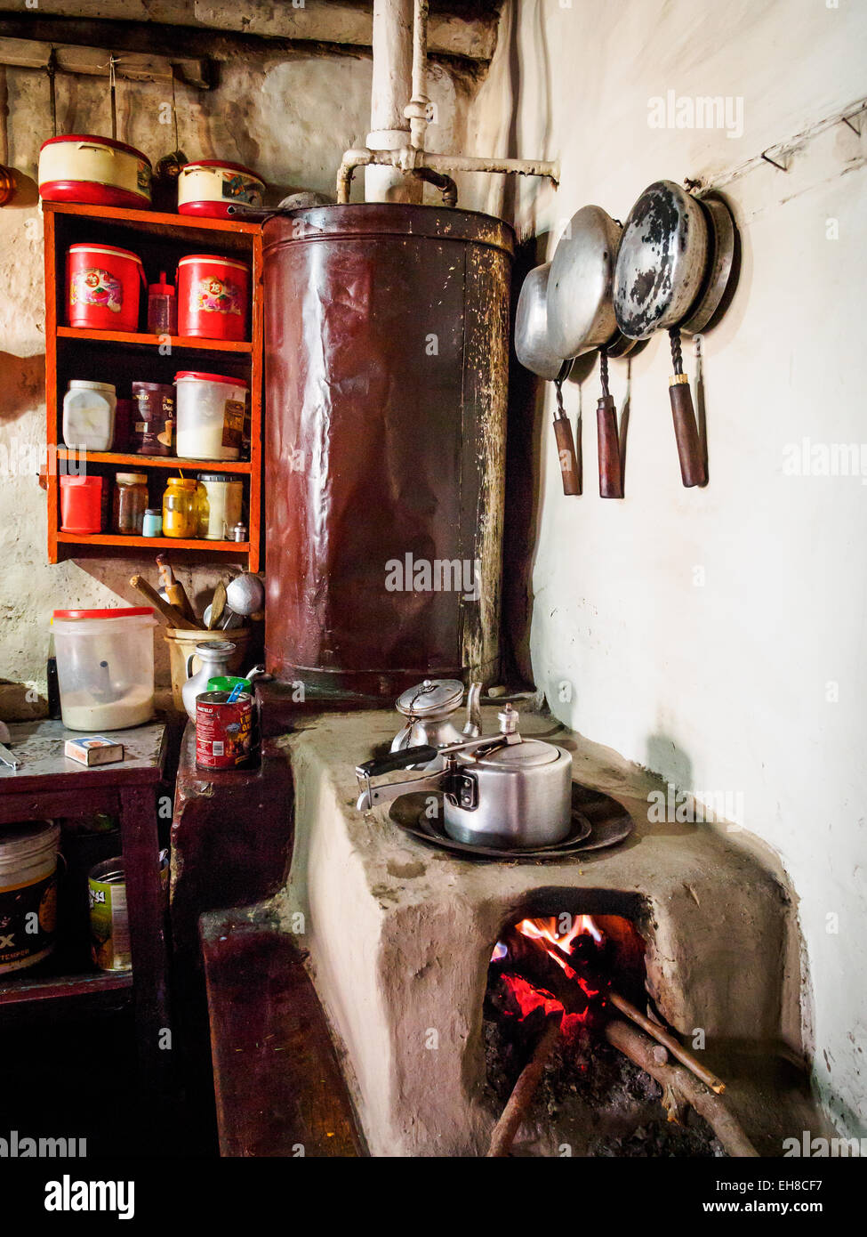 Pressure cookers on a clay stove in a guest house in the village of Ghami, Mustang, Nepal. - Stock Image