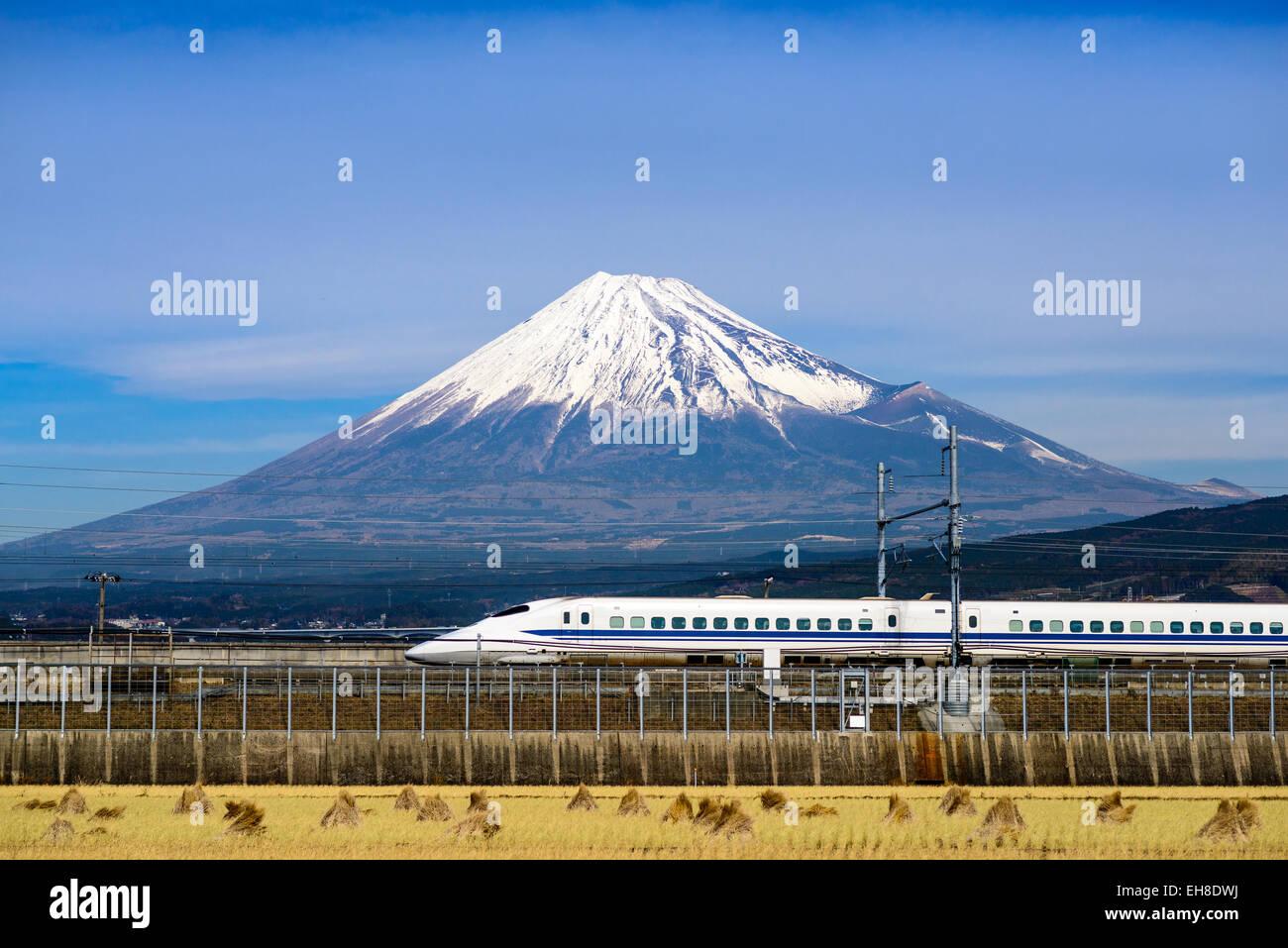 A bullet train passes below Mt. Fuji in Japan. - Stock Image