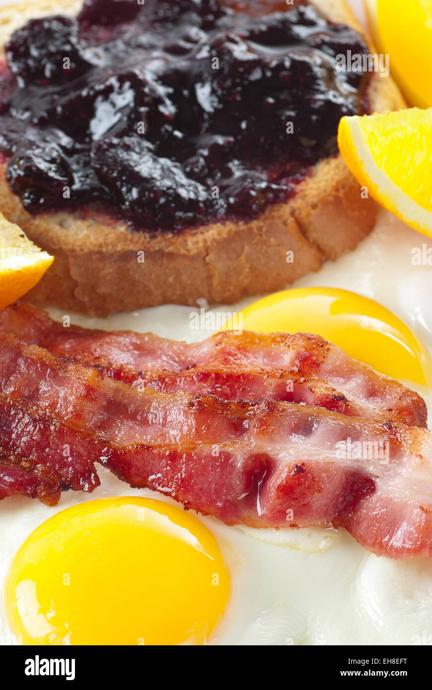 Bacon, fried eggs, orange and roasted bread with jam. - Stock Image