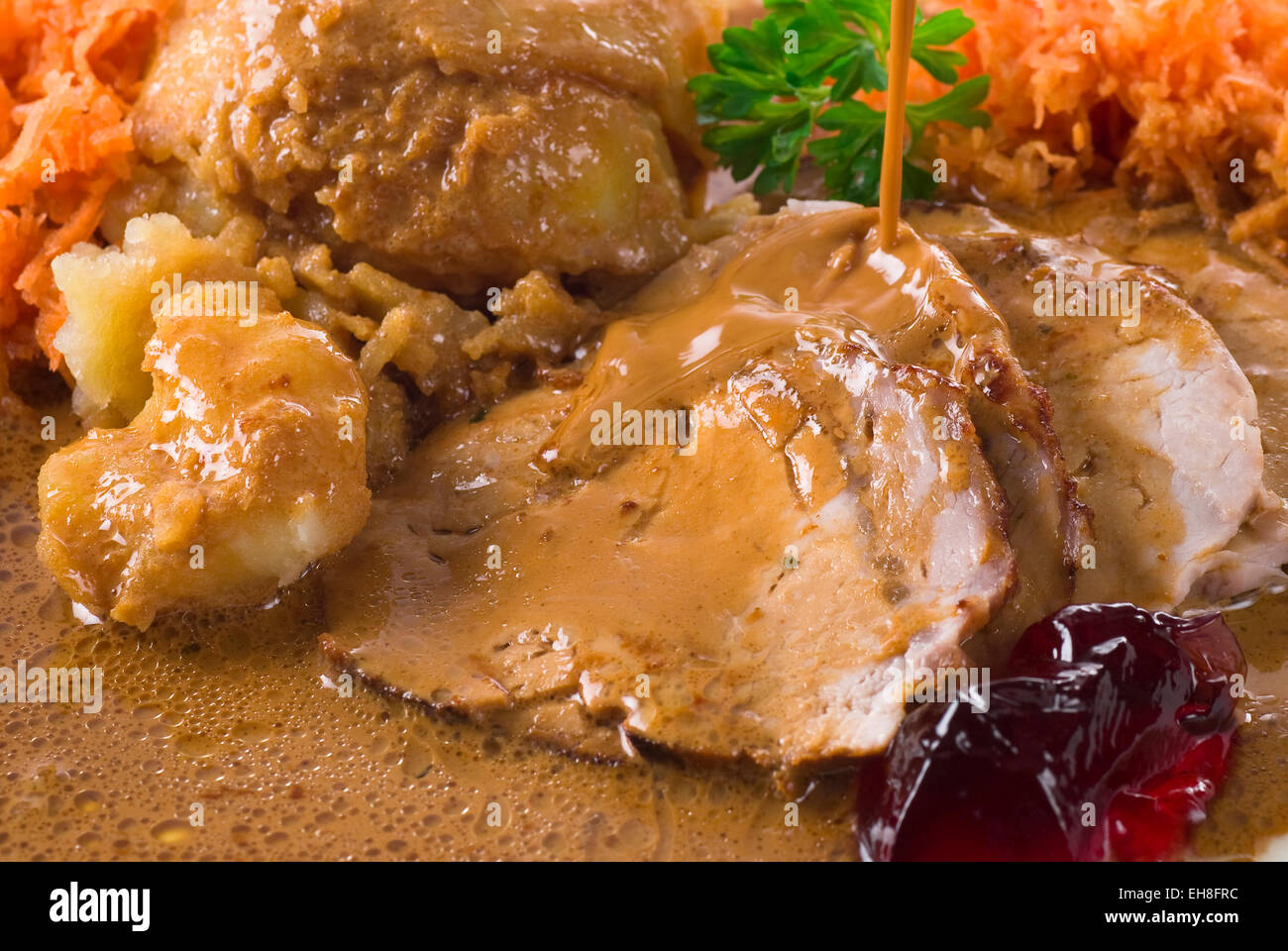 Sliced baked pork steak with cream sauce and cooked potato. - Stock Image