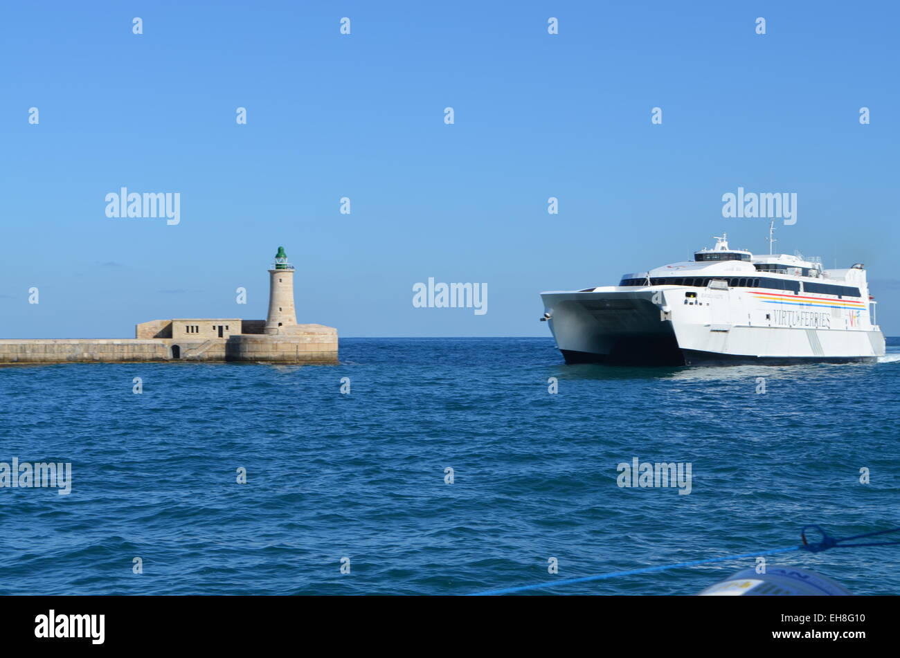 Valletta, Malta Harbour, Out to sea again and past the Harbour Lighthouse. We pass a large transport ferry coming - Stock Image