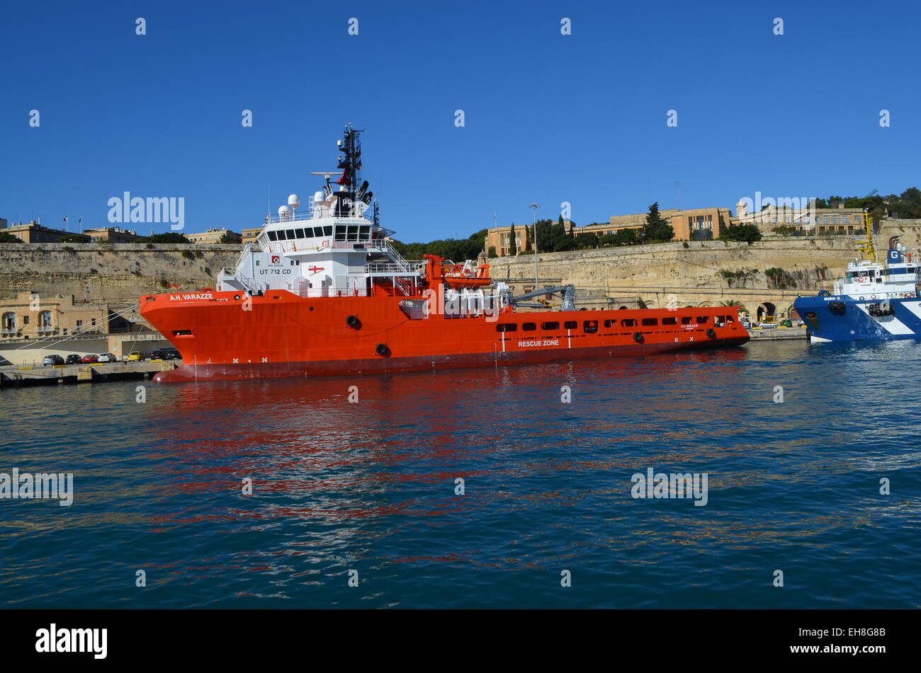 Cruising round the inner walls of the Grand Harbour we pass by another boat moored there under the packed city of - Stock Image