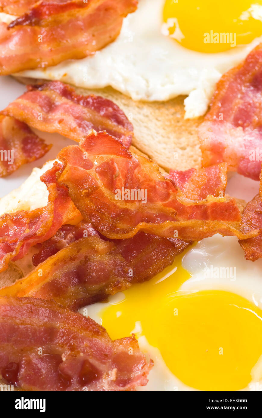 Fried bacon and eggs on white bread. - Stock Image