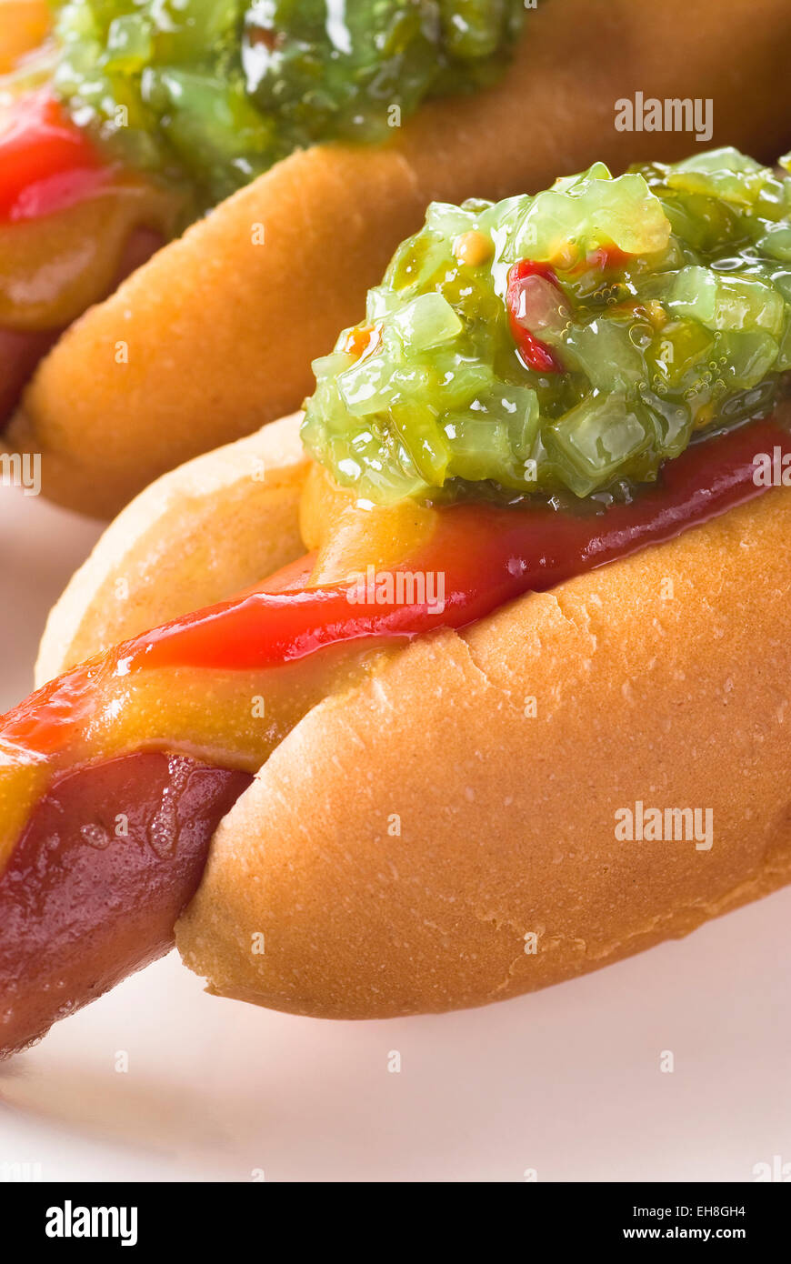 Sweet relish on grilled hot dog. Mustard and ketchup. - Stock Image