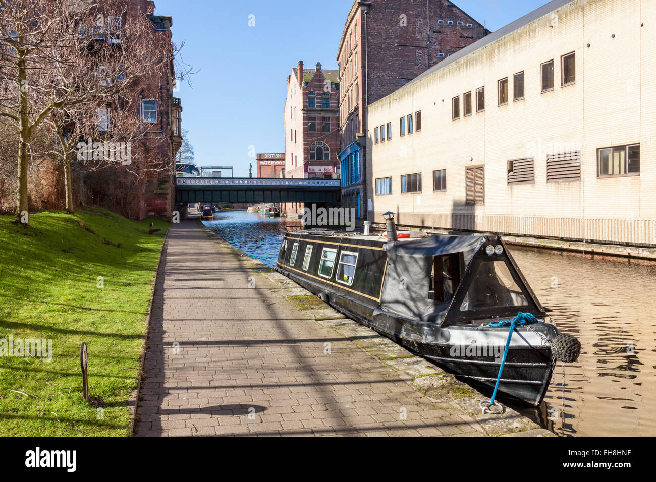 Narrowboat moored on an old waterway through a city. The Nottingham and Beeston Canal, Nottingham, England, UK - Stock Image