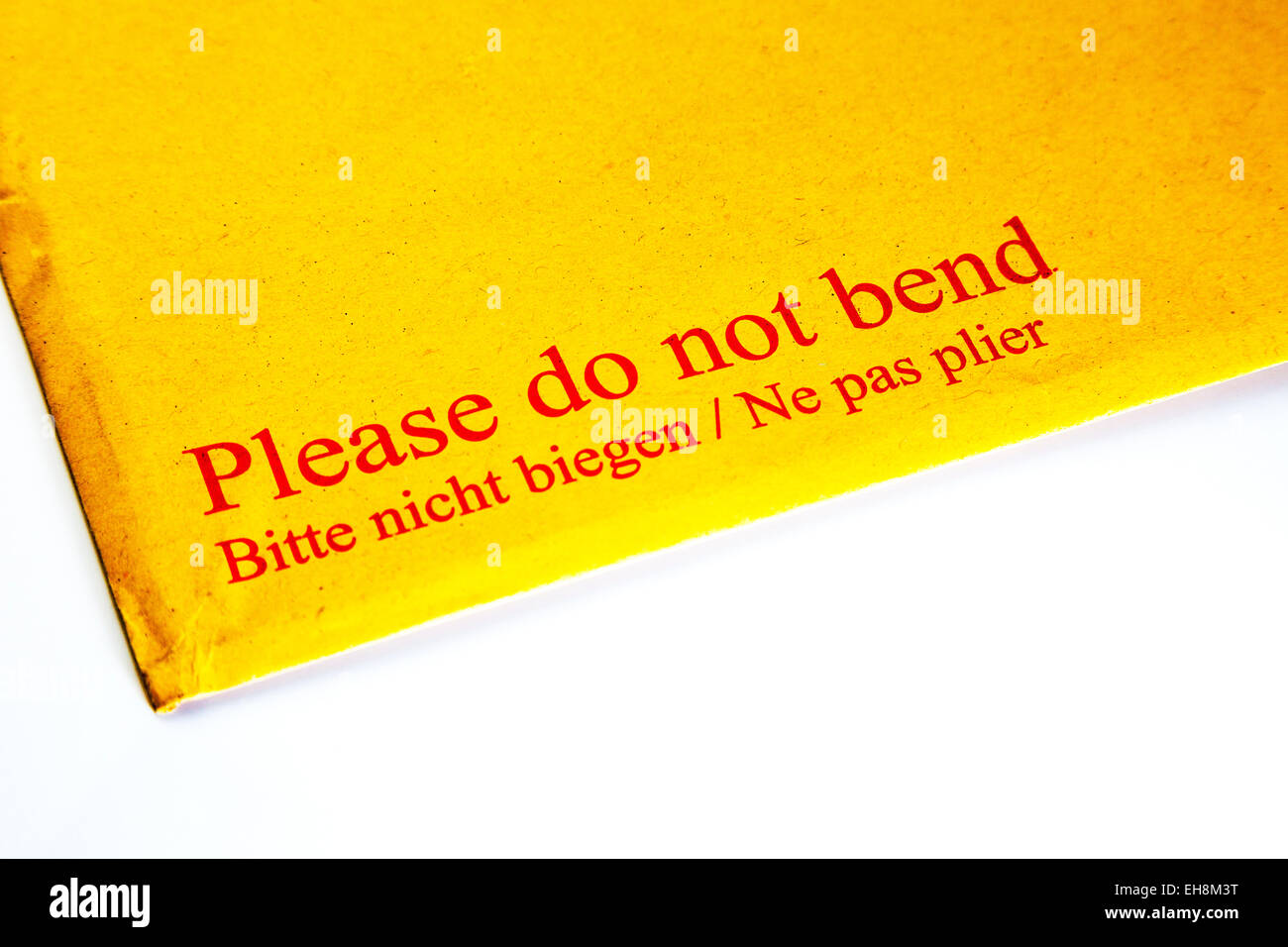 Please do not bend envelope letter written words bitte nicht biegen ne pas plier cutout white background copy space - Stock Image