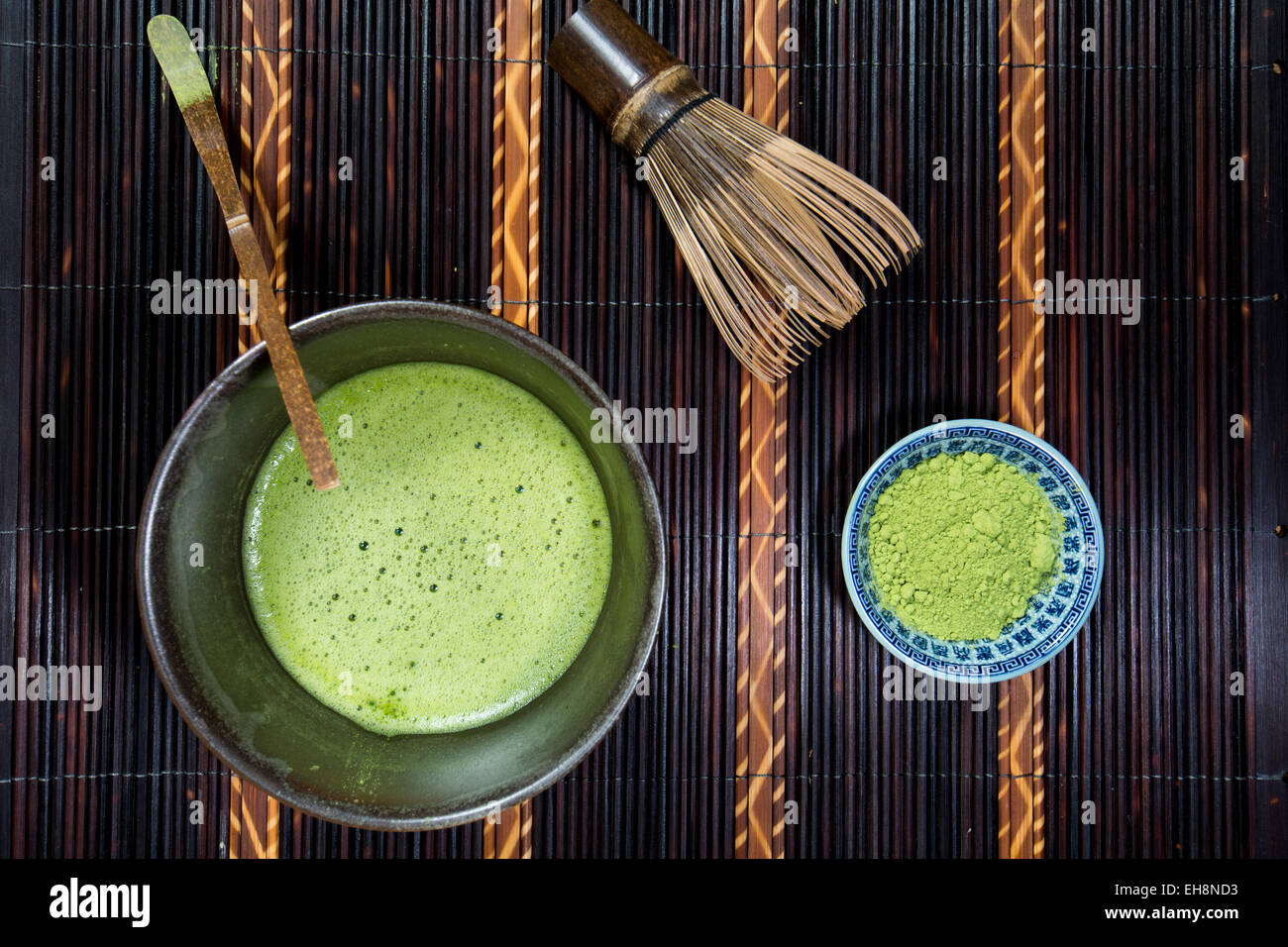 Bowl of Matcha with a Chasen a Chashaku and a bowl of Matcha powder on a place mat - Stock Image