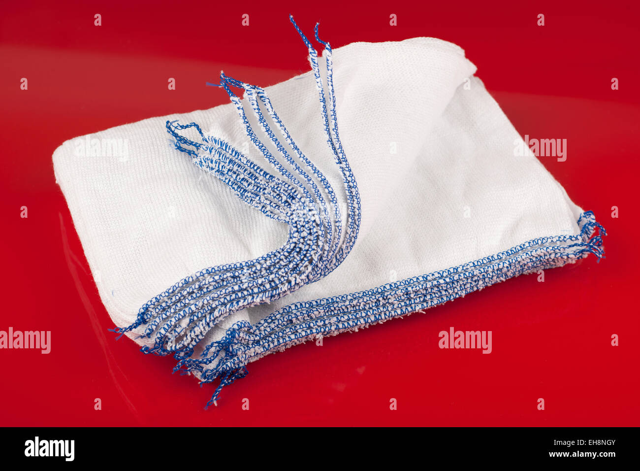 Pile of blue edged white dish cloths - Stock Image