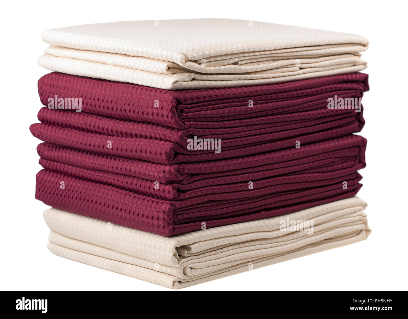 Pile of dark red and cream folded lined curtains - Stock Image