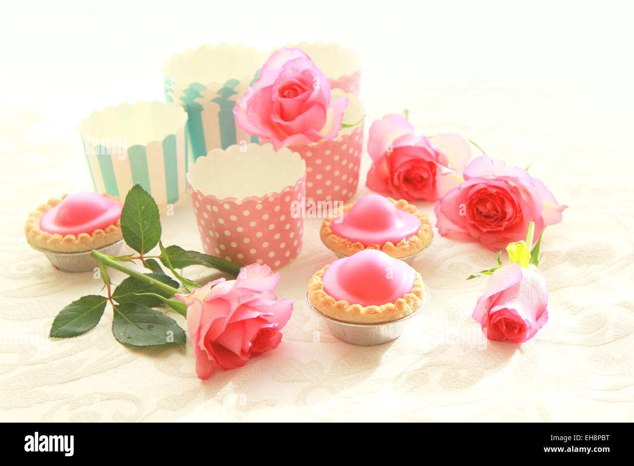 Pink cakes on blue plate with pink roses - Stock Image