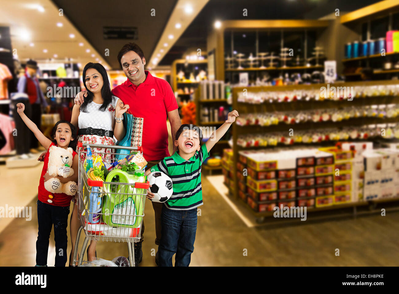 4 indian kids and Parents mall Trolley Shopping shouting - Stock Image