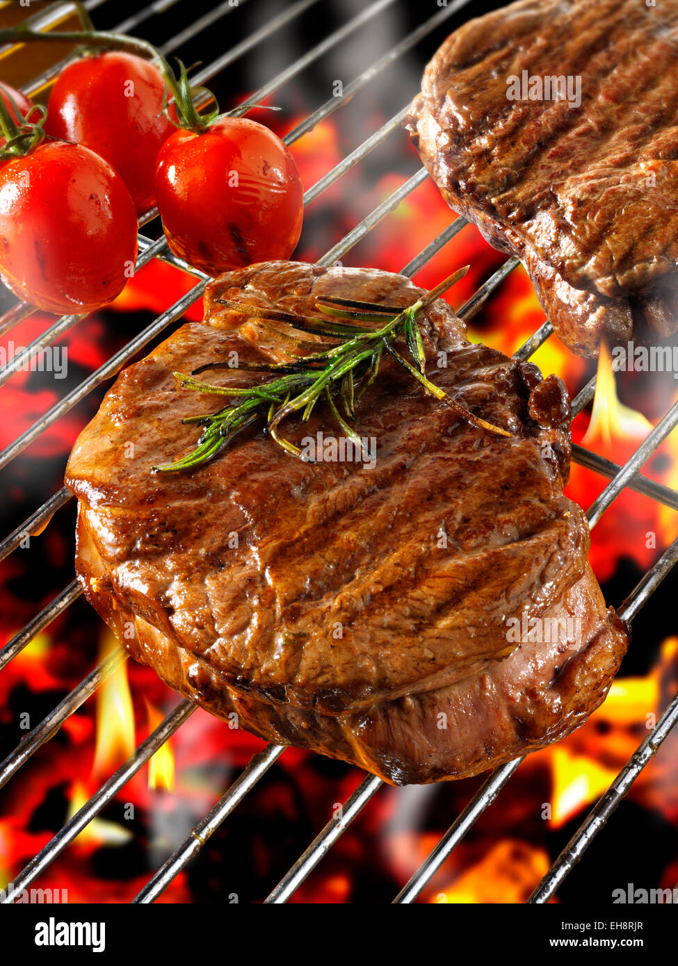 Barbecue steak cooking on a flame bbq grill - Stock Image