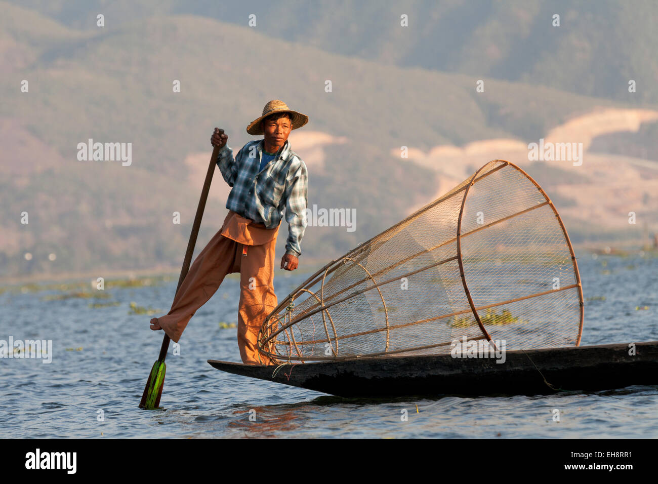 Leg rowing fisherman with cone shaped net; Inle Lake, Myanmar ( Burma ), Asia - Stock Image