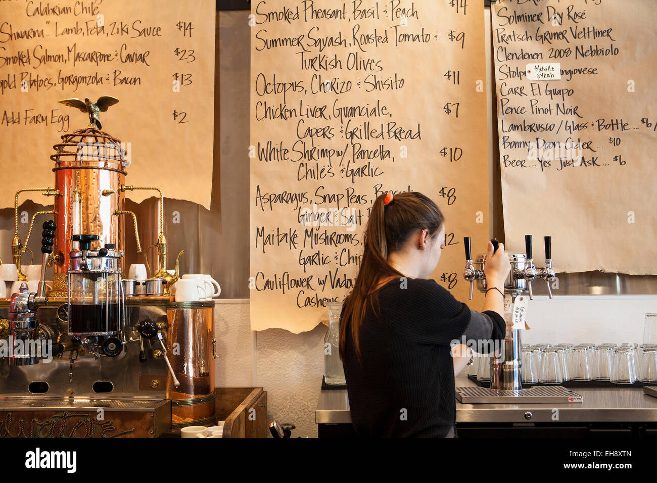 server pours a glass of viognier with menus on brown paper rolls, Industrial Eats, Buellton, California - Stock Image