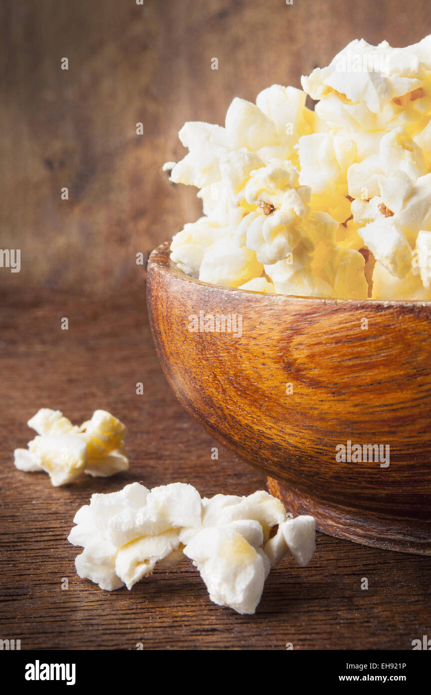 Fresh popcorn in bowl on wooden table - Stock Image