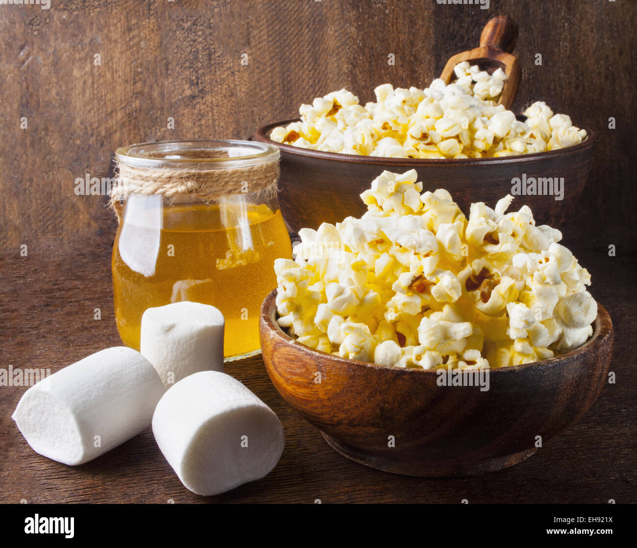 Fresh popcorn in bowl on wooden table. - Stock Image