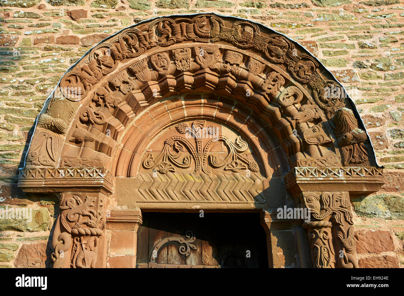 Norman Romanesque relief sculptures of dragons and mythical creatures Kilpeck Church, Herefordshire, England - Stock Image
