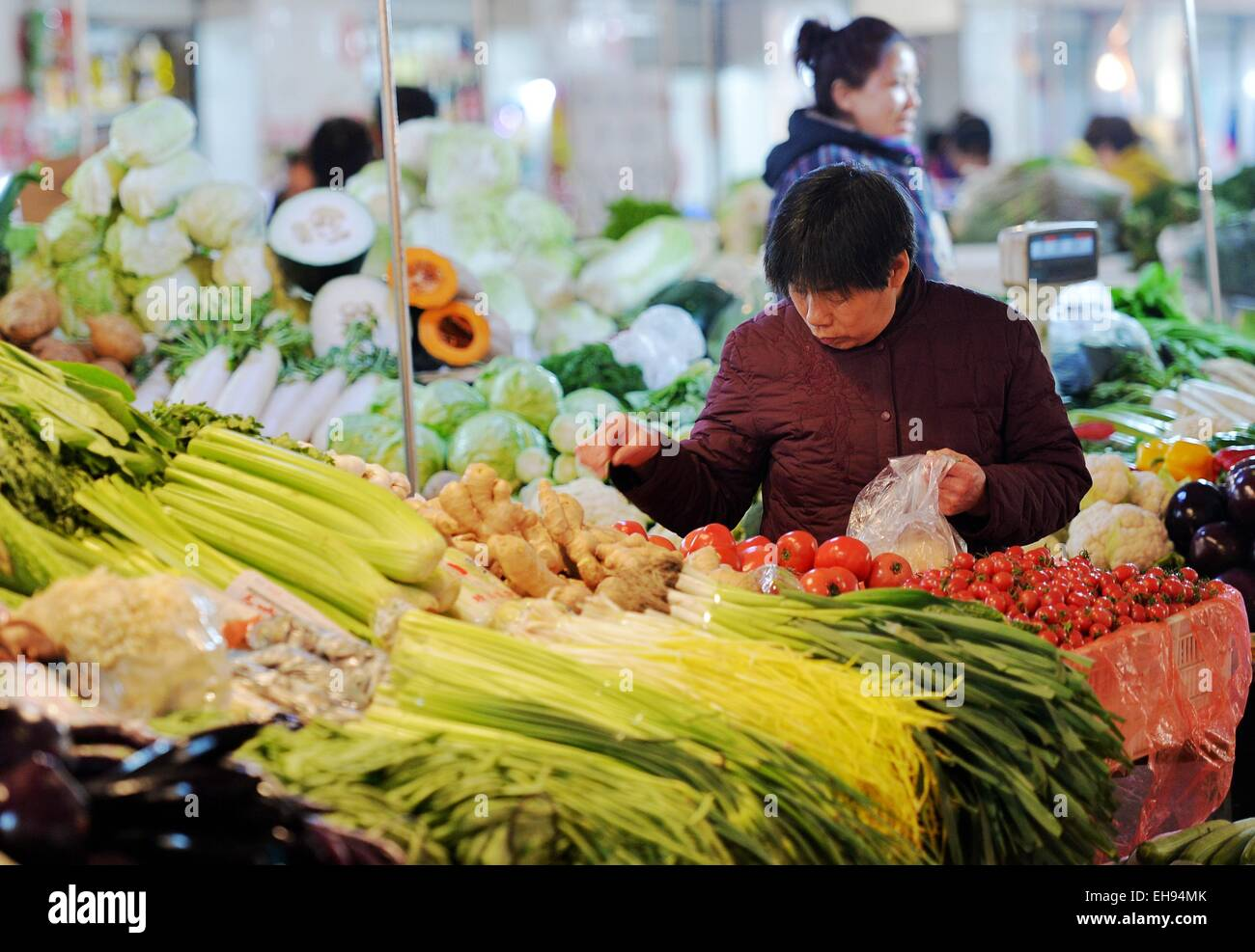 Shijiazhuang, China's Hebei Province. 9th Mar, 2015. A consumer selects vegetable at a farm product market in Shijiazhuang, Stock Photo