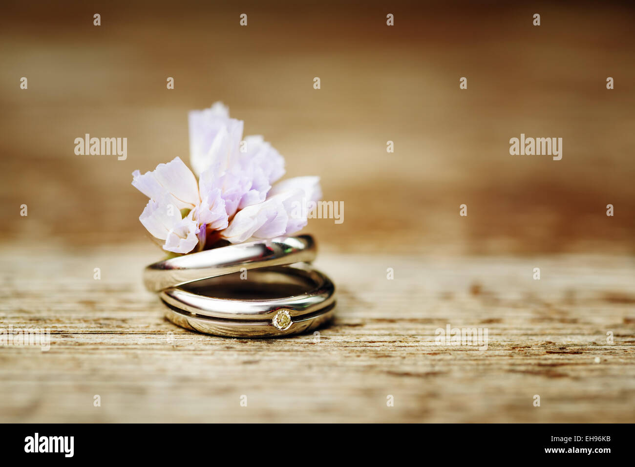 Wedding Engagement Rings Close Up With Cute Wild Flower On Wood Background Rustic Style Decoration Instagram Color Effect