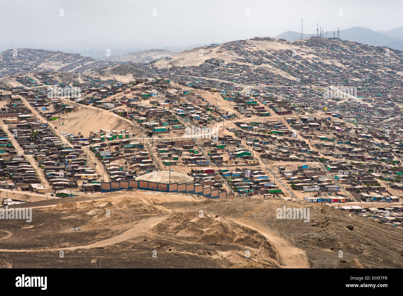 A sprawling settlement of houses and wooden shacks is seen on the dusty hillsides of Pachacútec, a desert suburb - Stock Image