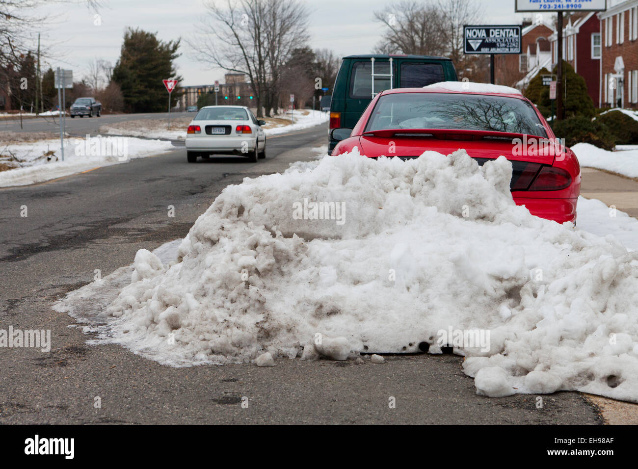 Street parked car blocked in by plowed snow - USA - Stock Image