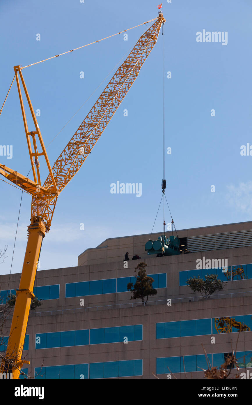 Telescopic boom crane picking up equipment from office tower roof - USA Stock Photo