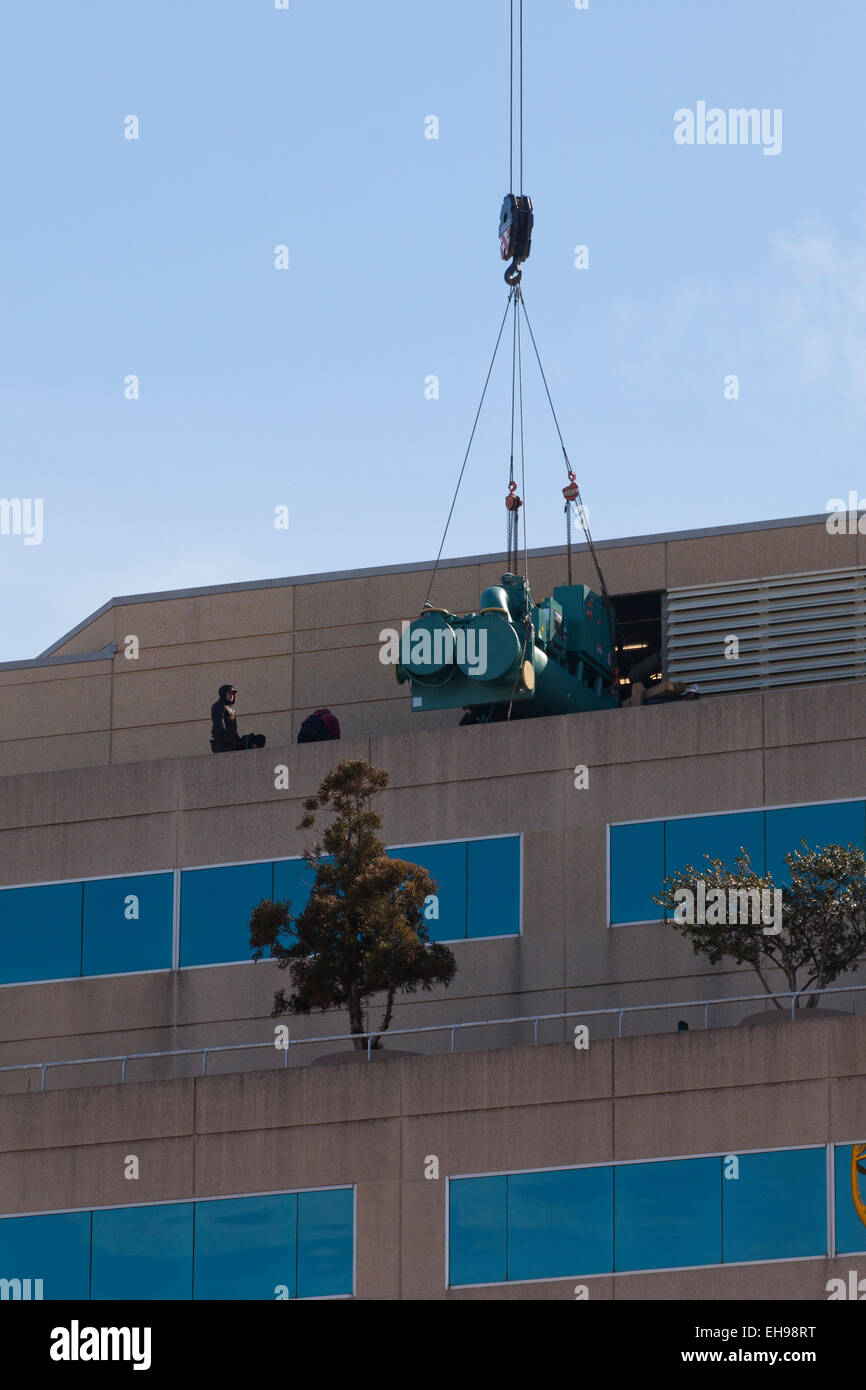 Workers monitoring equipment hoisted on crane cables on office tower roof - USA - Stock Image