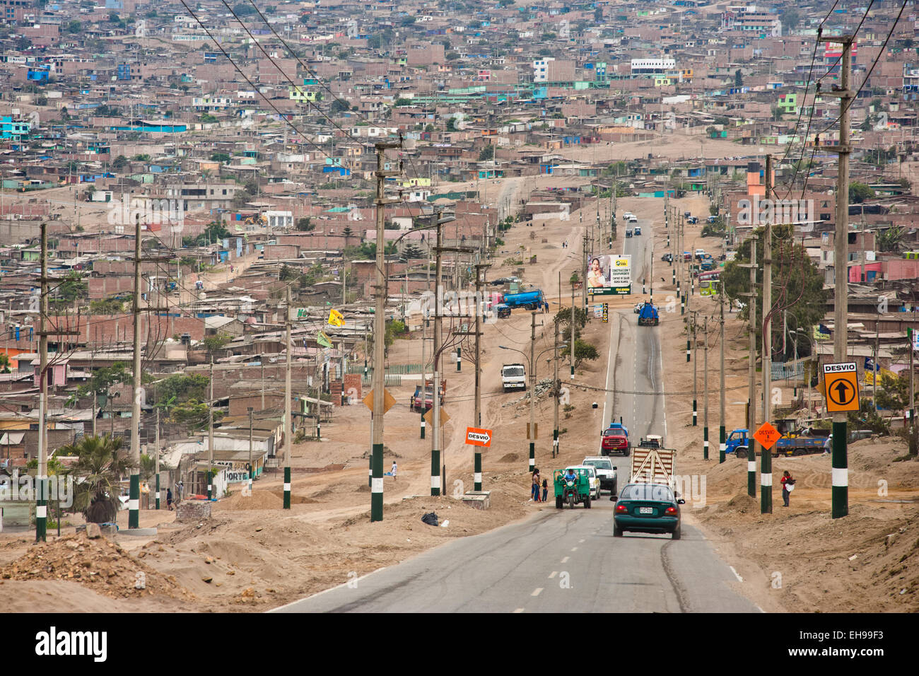 A sprawling settlement of houses, cut by a single road, is seen on the dusty hillsides of Pachacútec, Lima, - Stock Image