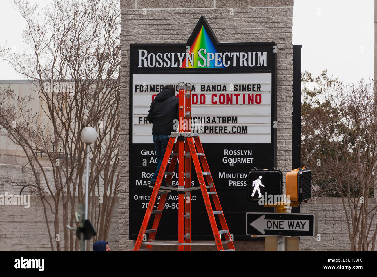 Worker making changes to marquee sign (letter board sign) - USA - Stock Image