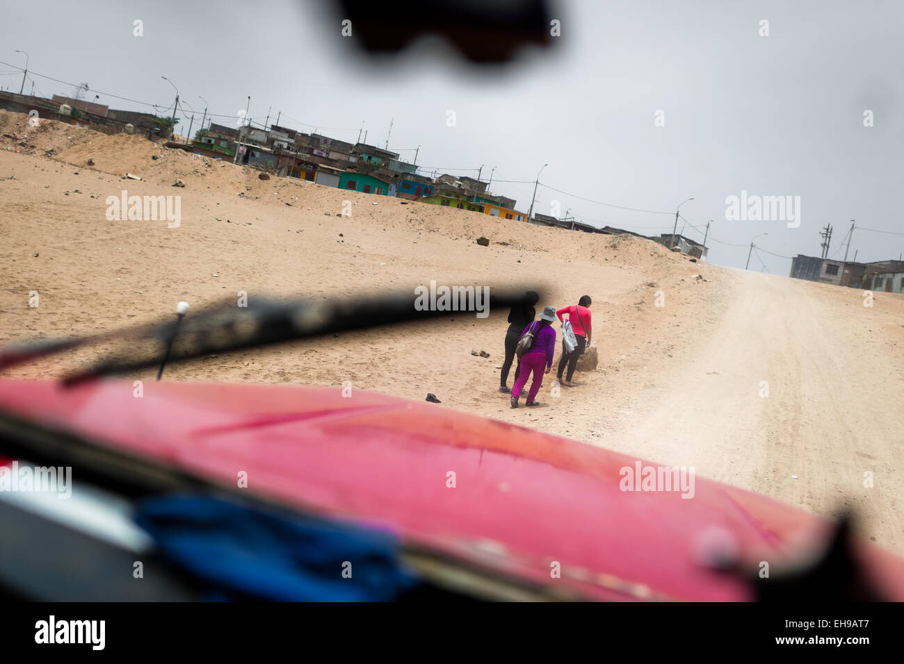 Peruvian women, climbing up a sandy path, are seen from a cabine of a water truck distributing drinking water in - Stock Image