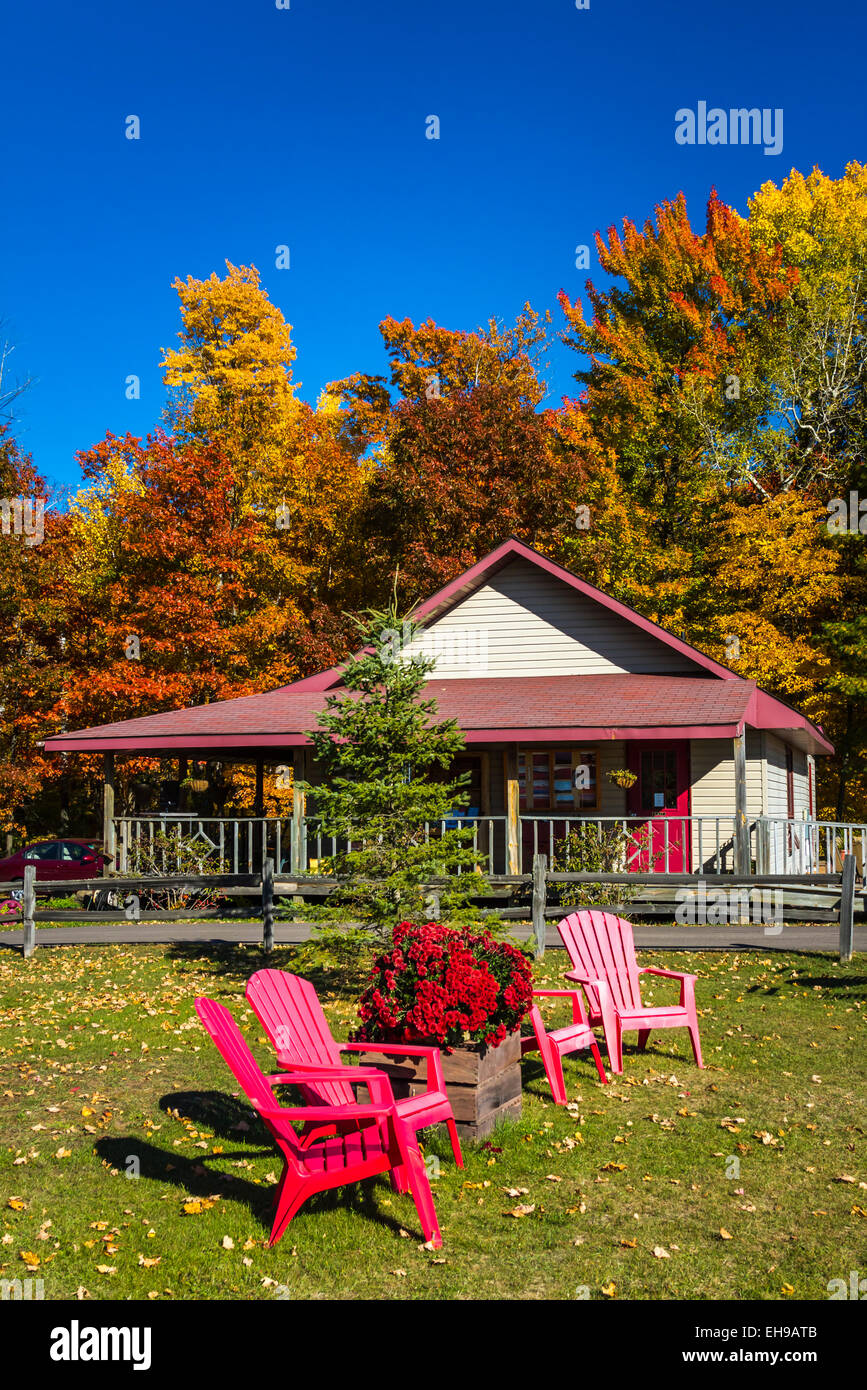 Lawn chairs and cottage with fall foliage color near Manitowish Waters, Michigan, USA. - Stock Image