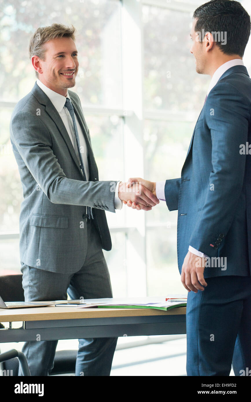 Businessmen shaking hands in office - Stock Image