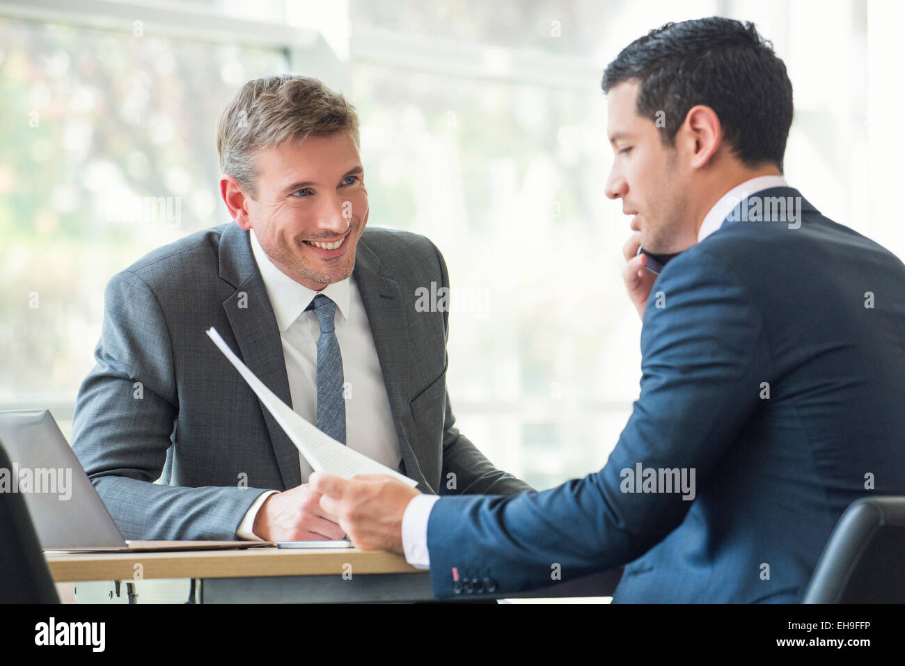 Businessmen discussing documents in meeting - Stock Image