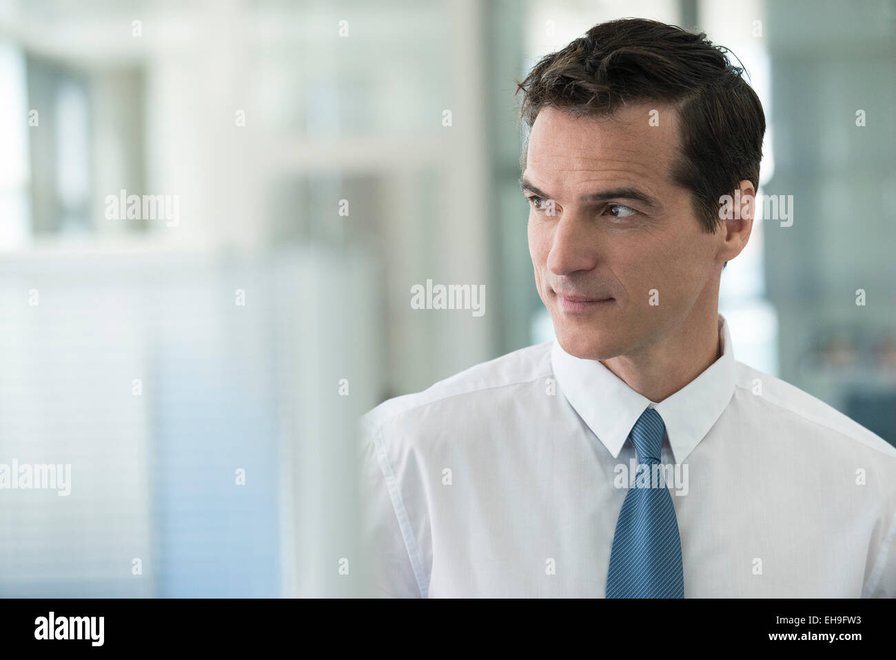 Businessman looking away in thought, portrait - Stock Image
