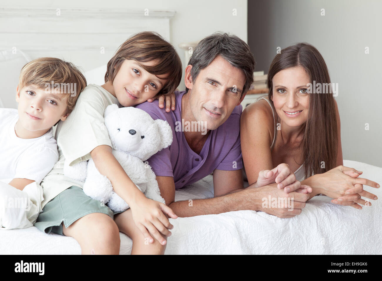 Parents and young sons relaxing together on bed, portrait - Stock Image