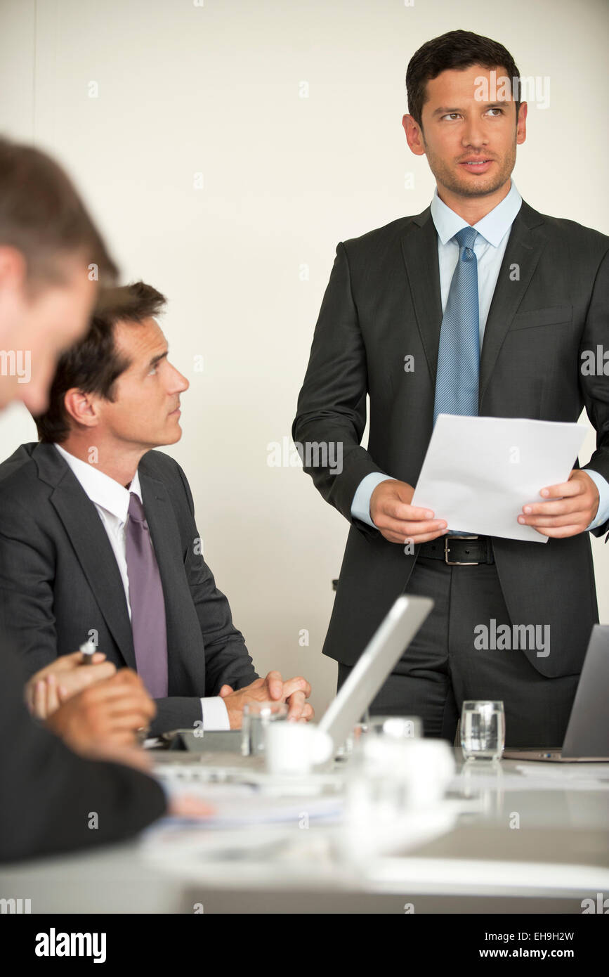 Businessman offering motivational speach at meeting - Stock Image