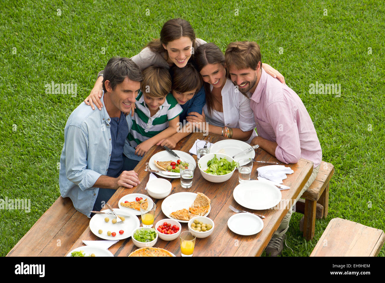 Family and friends huddle for group picnic photo - Stock Image
