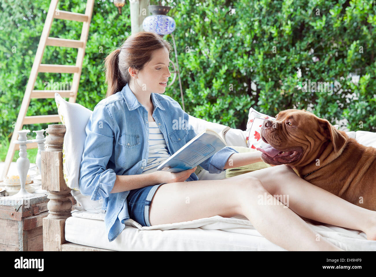 Young woman relaxing outdoors with dog - Stock Image