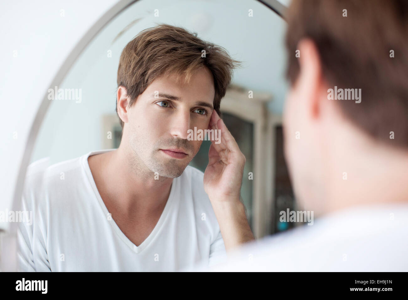 man looking at self in mirror with concerned look stock photo