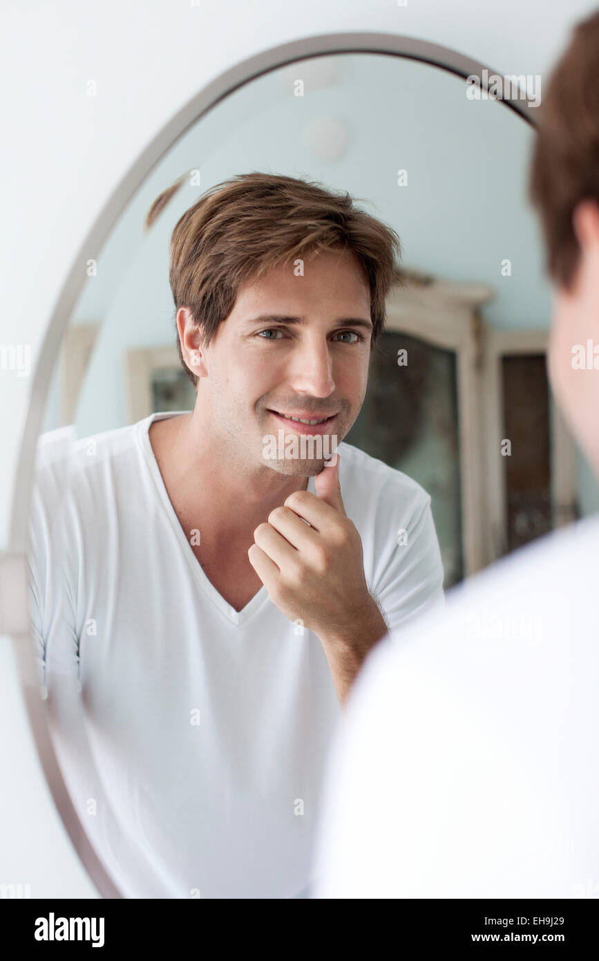 Man looking at self in mirror touching facial stubble - Stock Image
