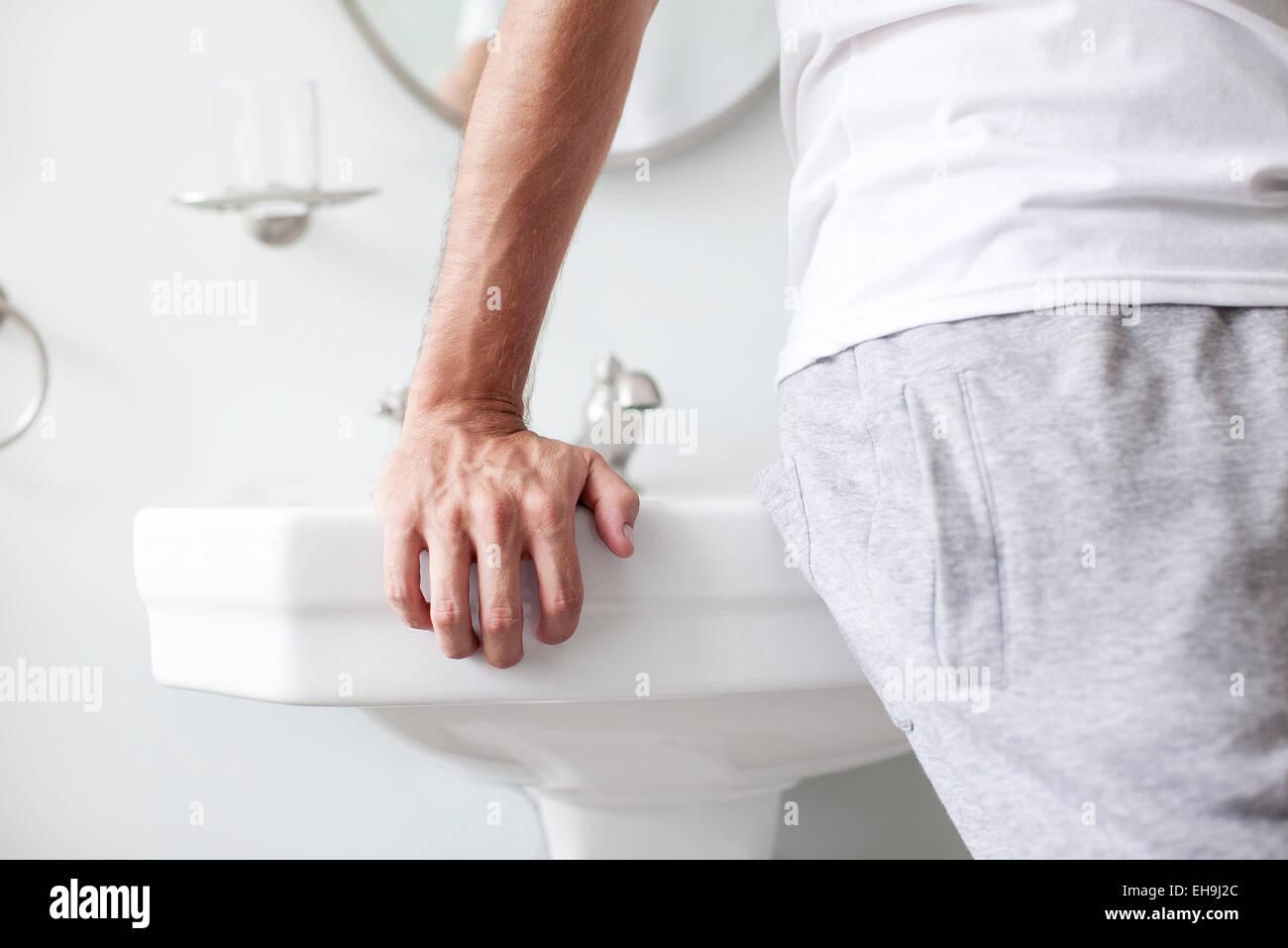 Man leaning against bathroom sink - Stock Image