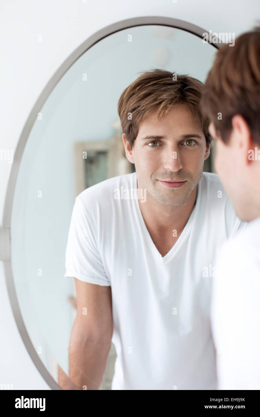 Man looking at self in mirror - Stock Image