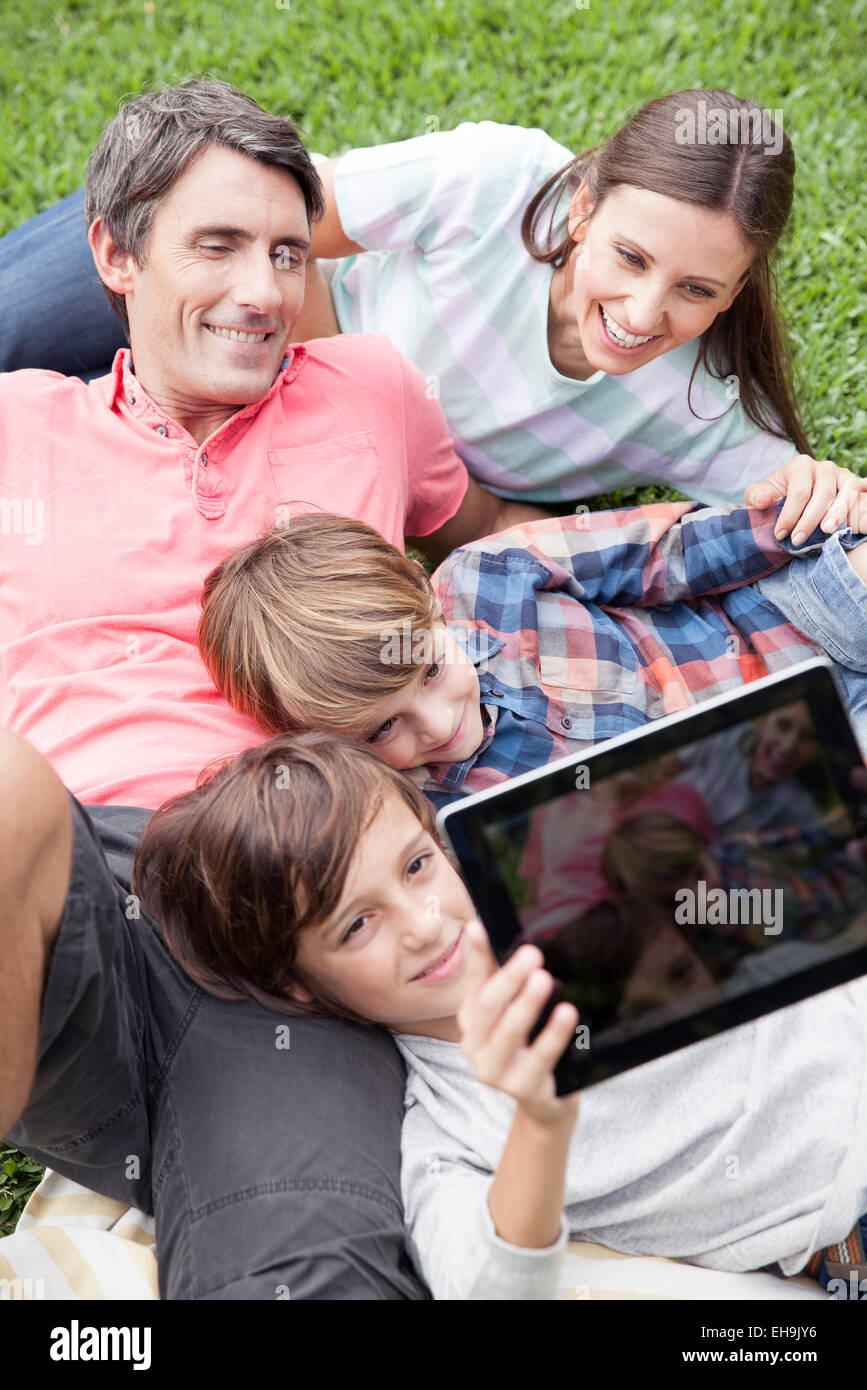 Boy photographing family with digital tablet camera Stock Photo