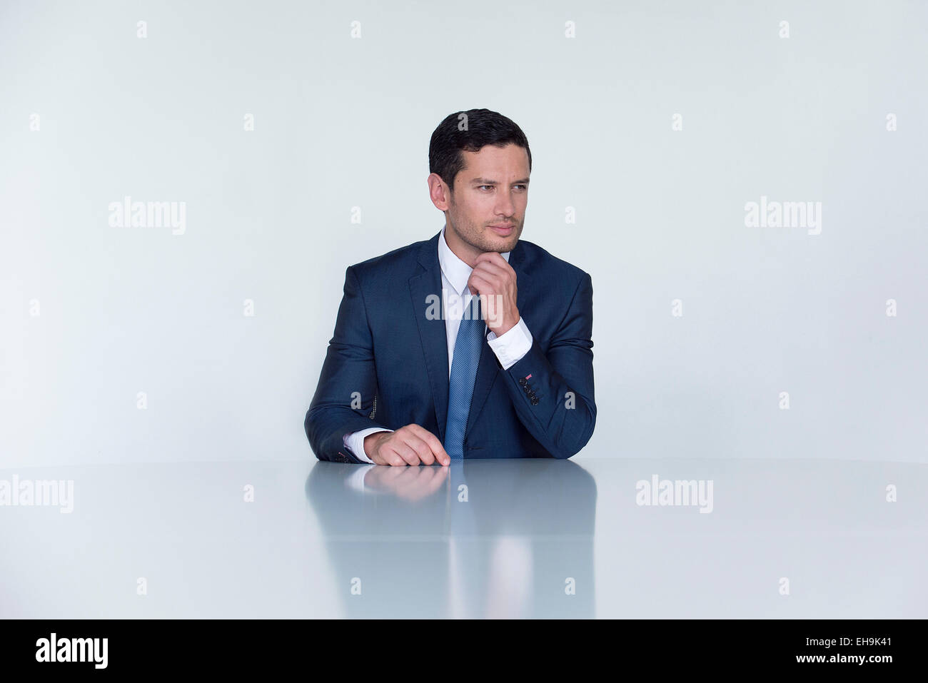 Businessman seated at table, looking away in thought - Stock Image