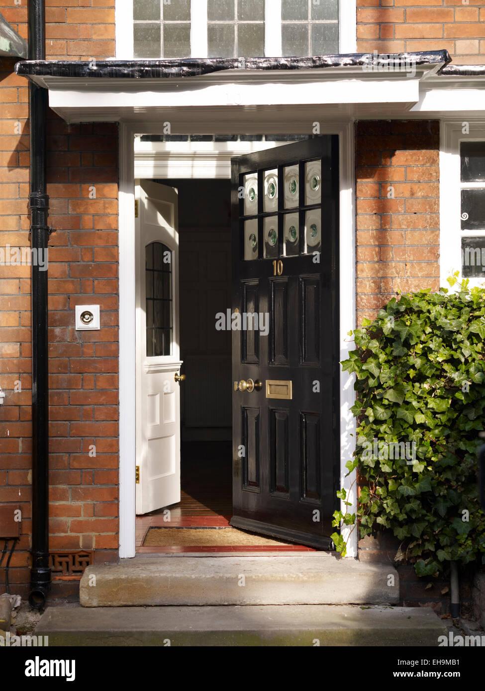 Open traditional black front door of redbrick residential ...