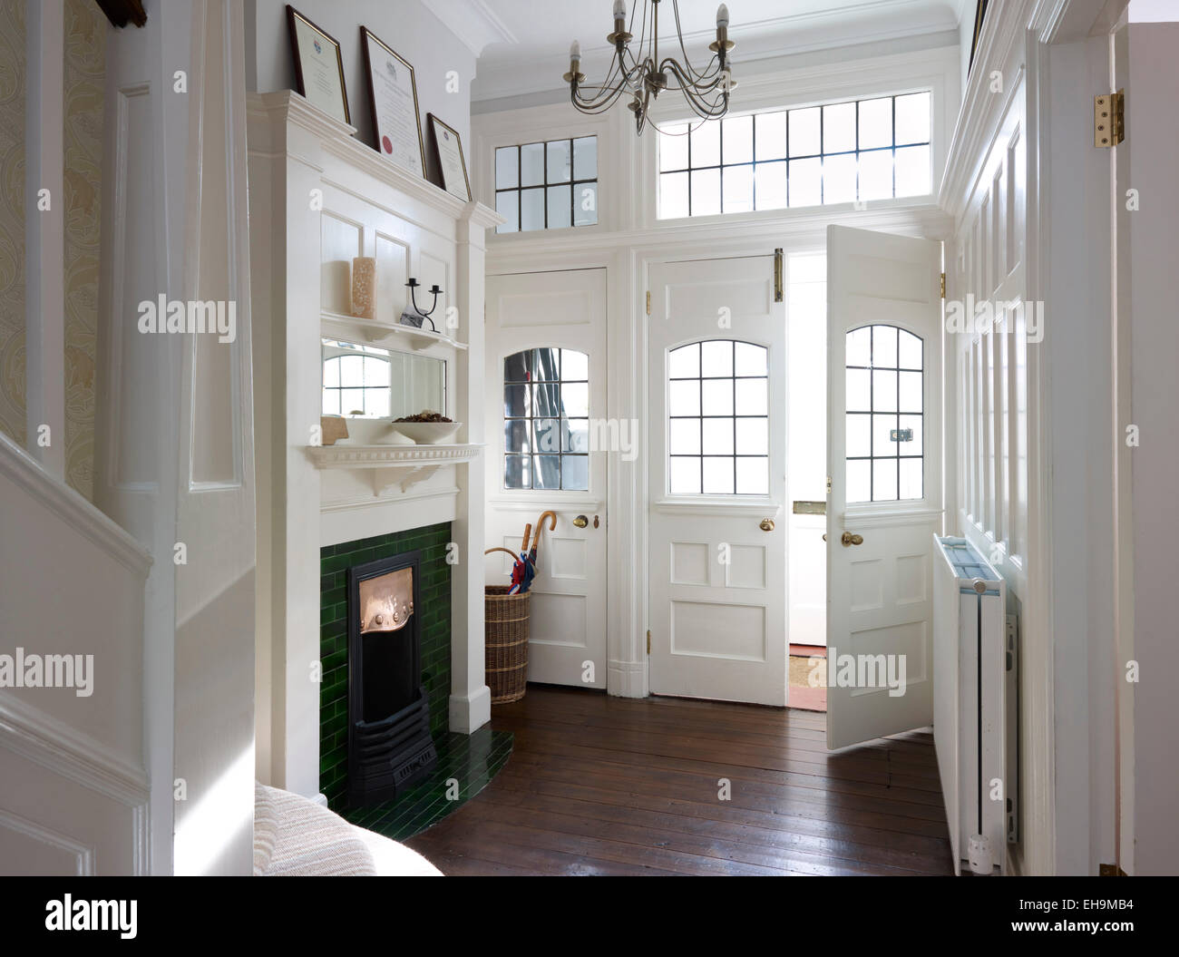 White entrance hall with green fireplace and dark wood flooring, Edwardian, residential house, Kingsmead, UK - Stock Image