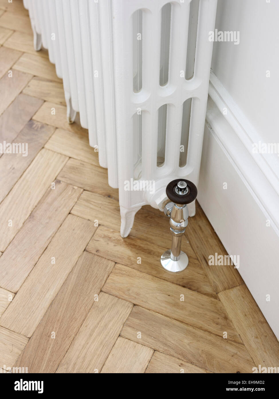 White Radiator And Herringbone Parquet Wooden Flooring