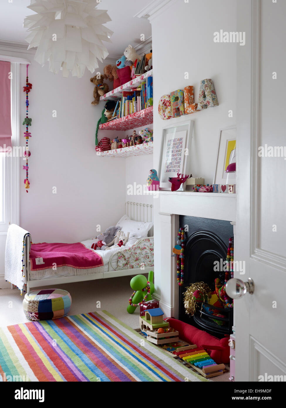 Bed and striped rug in white child's bedroom, residential house, Port Hall Street, Brighton, East Sussex, UK - Stock Image